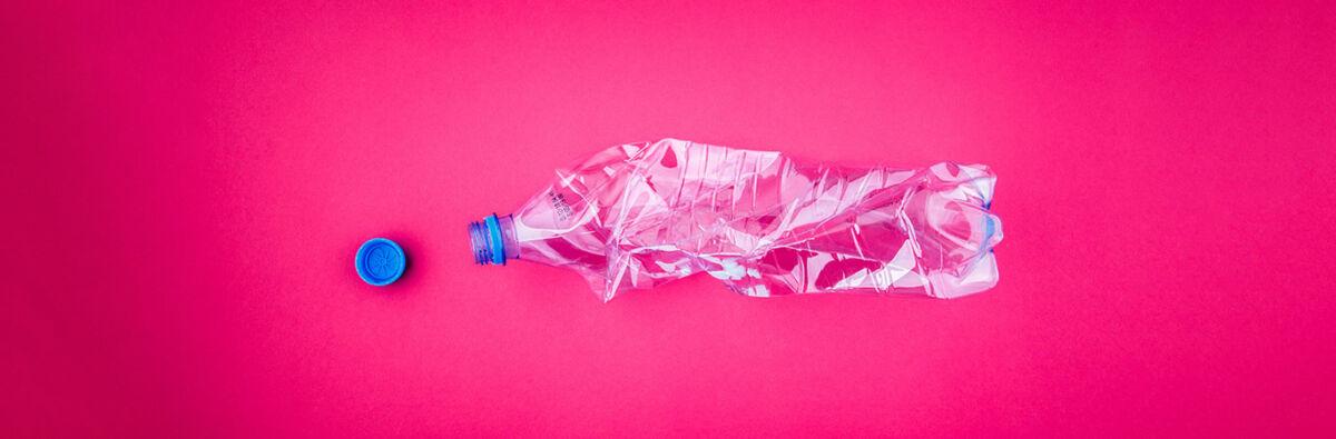 crushed plastic bottle on pink background