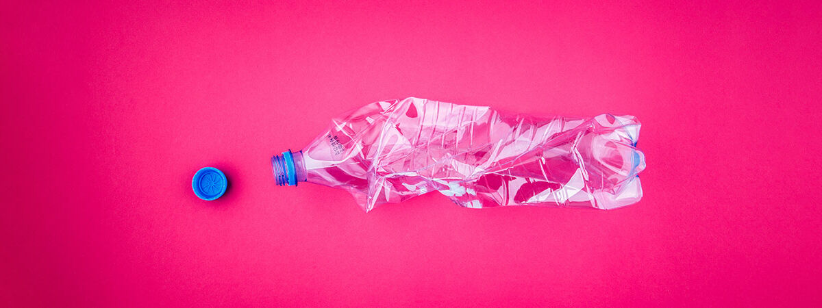crushed plastic bottle on pink background