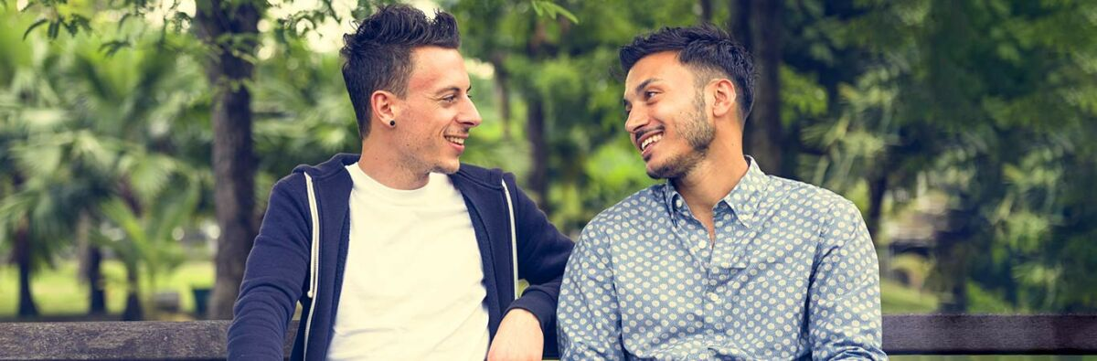 two guys on a date sitting on a park bench