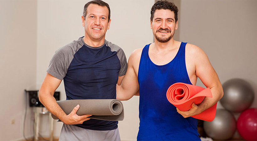 two men carrying yoga matts after a workout