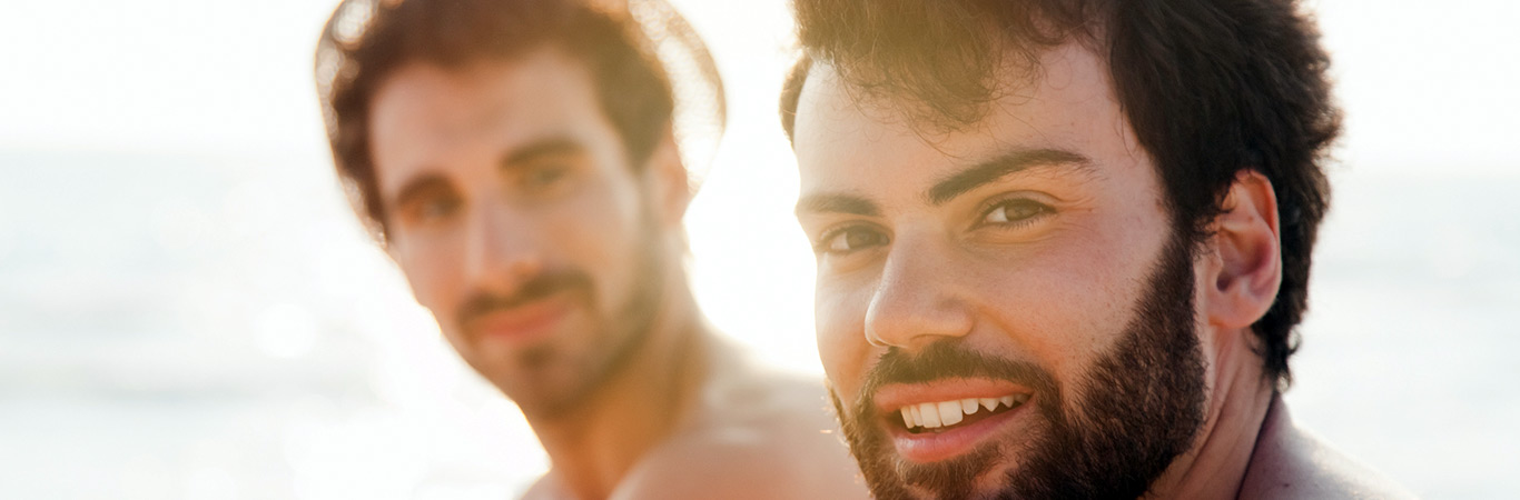 Two guys smiling and sitting by the sea