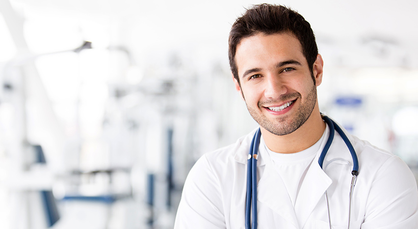 male doctor smiles with stethoscope round his neck