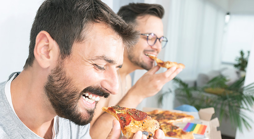 two male friends share a pizza together at home