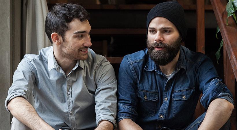 two male friends sit on steps deep in conversation