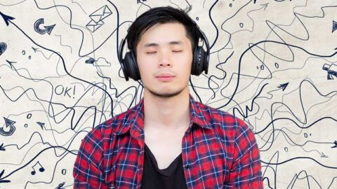 young man in plaid shirt chills with headphones against a backdrop of chaos