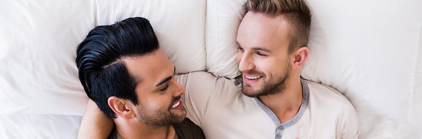 two guys fully clothed on a bed in warm embrace