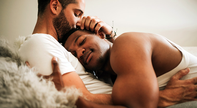 two guys sharing a cuddle on a furry blanket