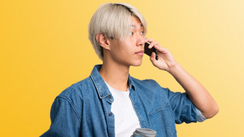 Man with bleached hair has important conversation on mobile phone holding coffee cup
