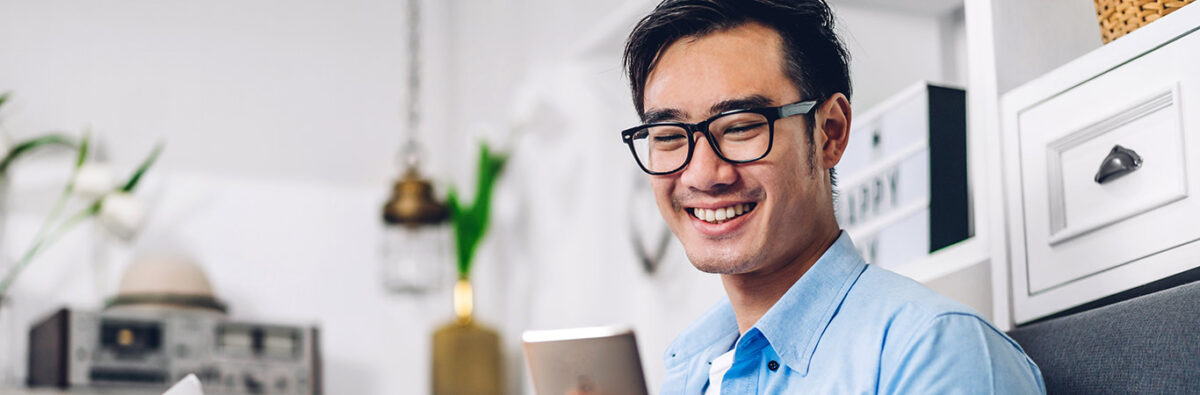 happy man with glasses looks at his mobile phone at home