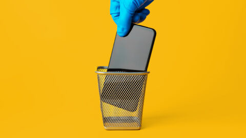 Blue gloved hand puts mobile phone in waste bin