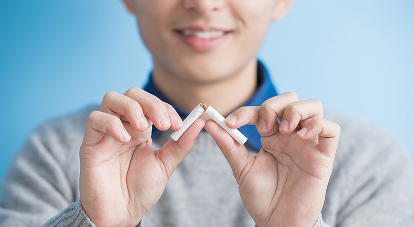 asian man breaks a cigarette in two to stop smoking