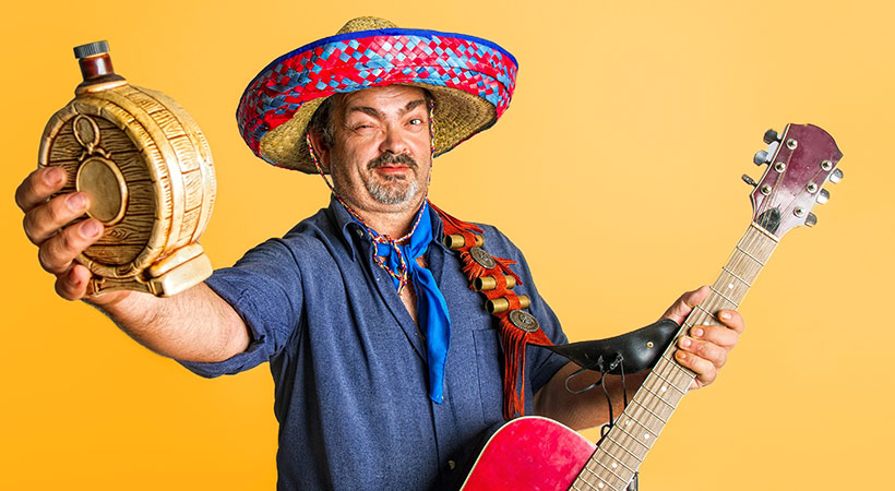 mexican man holds tequila bottle and guitar with inebriated look on face