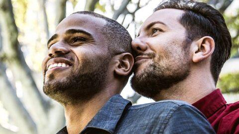 mixed race gay couple enjoying a hug outside