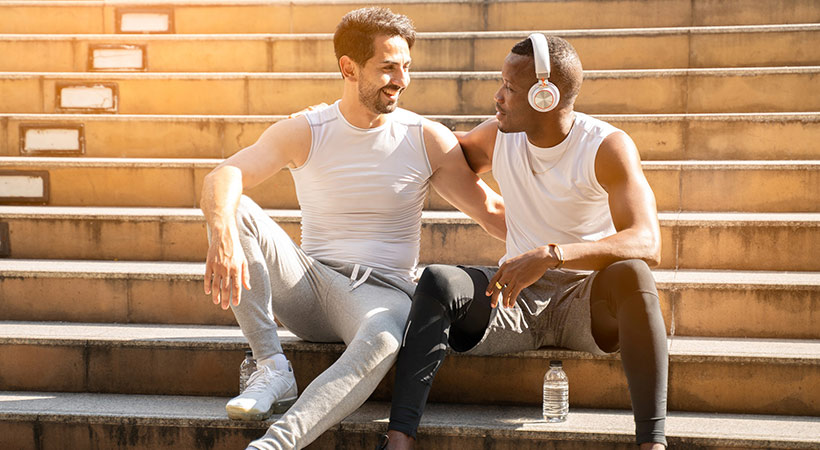 sporty mixed race gay couple sitting on steps together after jogging